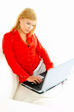 househould: Young pretty women on couch relaxing and using laptop computer Stock Photo