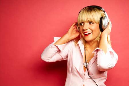 Young beautiful happy women listening music in headphones photo