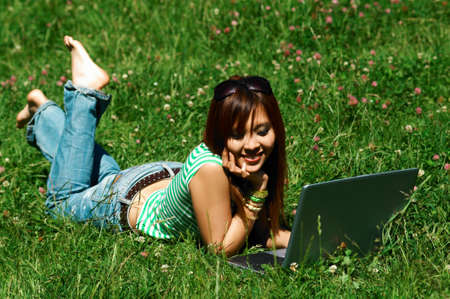 daydream: Beautiful asian young girl with laptop computer on meadow