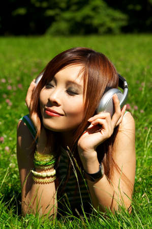 Beautiful asian young girl with headphones, listen to music on meadow photo