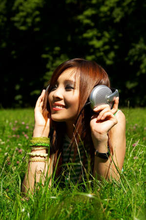 daydream: Beautiful asian young girl with headphones, listen to music on meadow