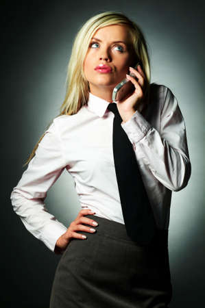 Young Business woman wearing white shirt and black tie talking cell phone photo
