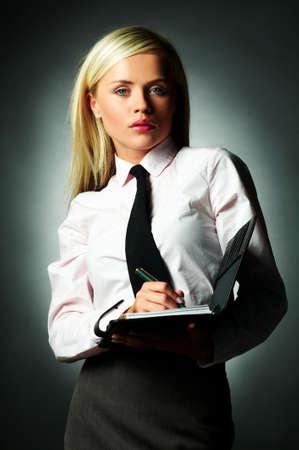 note book: Business giovane donna indossa una maglietta bianca e cravatta nera e nota libro
