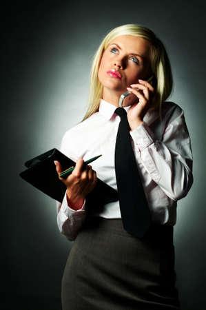 note book: La camicia bianca da portare giovane della donna di affari ed il legame nero ed il taccuino che usando la cellula telefonano