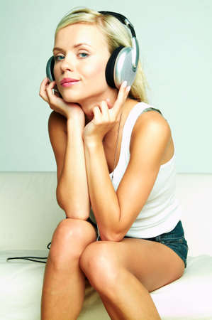 Young beautiful happy women listening music in headphones photo