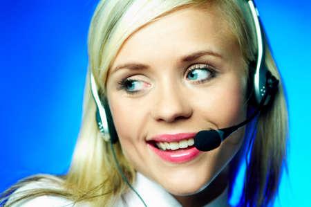 lazo negro: La camisa blanca que usa joven atractiva de la mujer de negocios y el lazo negro con el funcionamiento del receptor de cabeza como llamada centran el agente