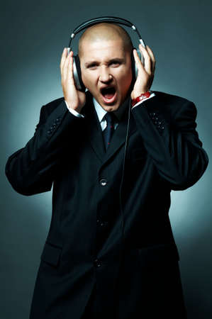 A Young businessman with headphones listen to the music photo