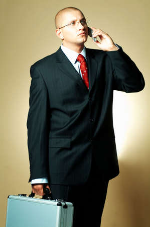 A businessman wearing black suit, using cell phone and holding case Stock Photo - 494955