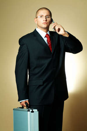 A businessman wearing black suit, using cell phone and holding case Stock Photo - 494906