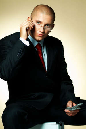 A businessman wearing black suit, using cell phone and sitting on case Stock Photo - 494978