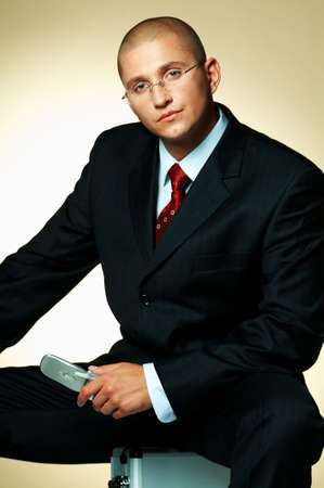 A businessman wearing black suit, using cell phone and sitting on case Stock Photo - 495013