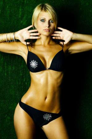 Portrait of beautiful young sexy woman wearing bikini on green artificial grass photo