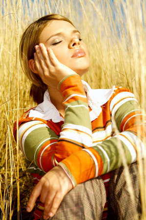 Young business woman relaxing on golden meadow Stock Photo - 547415