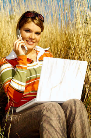 Young business woman relaxing, working on laptop computer and talking cell photn on meadow photo