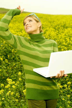 Young business woman with laptop computer on green meadow full of yellow flowers photo