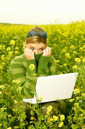 Joven mujer de negocios con el ordenador portátil sobre la verde pradera llena de flores amarillas  Foto de archivo - 547375