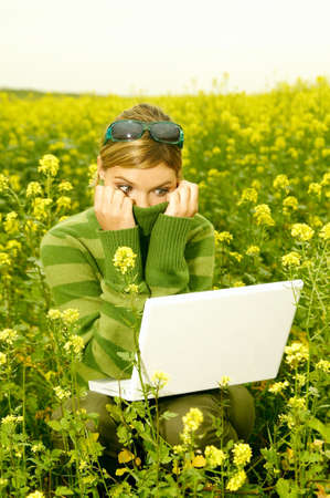 Young business woman with laptop computer on green meadow full of yellow flowers Stock Photo - 547375