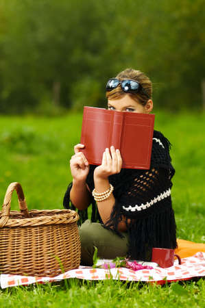 Young business woman with book during picnic on green meadows outdoors Stock Photo - 550889