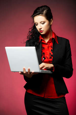 Young Business woman wearing red shirt and black jacket with laptop computer photo