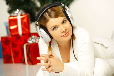 Young beautiful woman next to christmas tree and presents listen to music in headphones photo