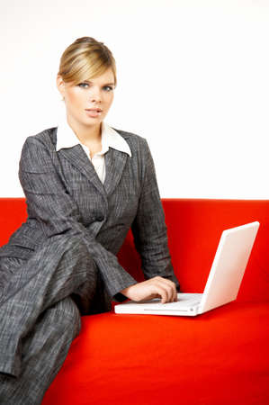 outwork: Young women is resting on the couch and surfing the internet on her laptop computer