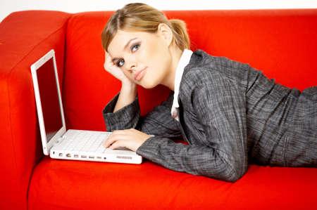 outwork: Las mujeres j�venes se est�n reclinando sobre el sof� y est�n practicando surf el Internet en su computadora de computadora port�til