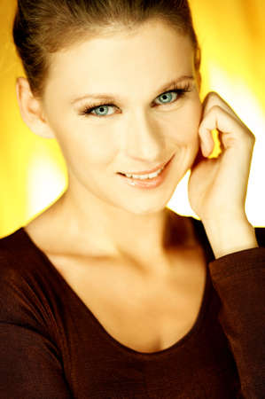 Portrait of attractive beautiful young woman posing on yellow background photo