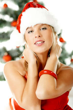 Beautiful young woman next to christmas tree wearing santas hat on white background photo