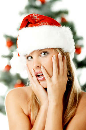 Beautiful young woman next to christmas tree wearing santas hat on white background Stock Photo - 606604