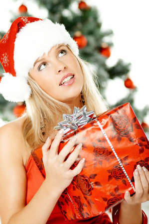 Beautiful young woman next to christmas tree wearing santas hat on white background Stock Photo - 606602