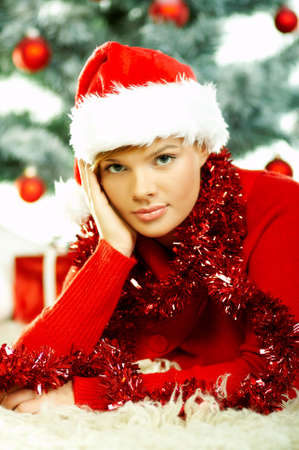 Beautiful young woman wearing santas hat next to christmas tree on white background Stock Photo - 610679