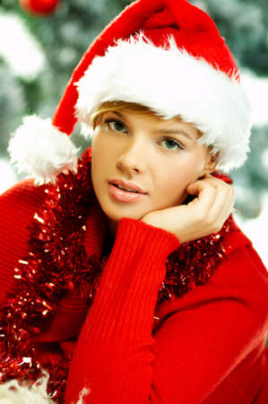 Beautiful young woman wearing santas hat next to christmas tree on white background Stock Photo - 610681