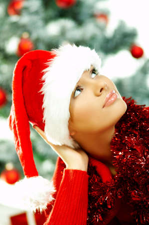 Beautiful young woman wearing santas hat next to christmas tree on white background Stock Photo - 610682