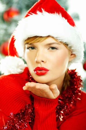 Beautiful young woman wearing santas hat next to christmas tree on white background Stock Photo - 610630