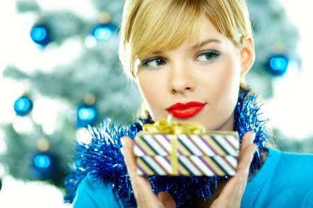 Beautiful young woman next to christmas tree on white background photo