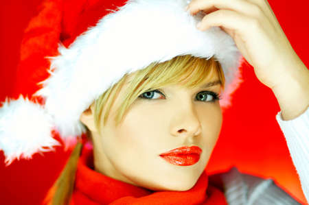 Portrait of beautiful blond young woman wearing santa claus hat on red background photo
