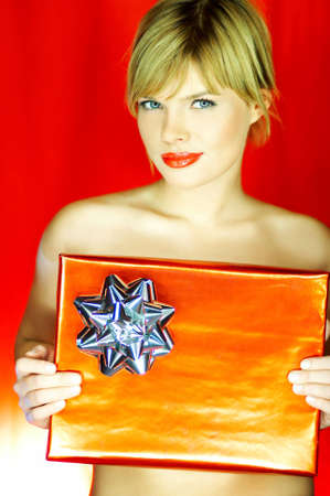 Portrait of beautiful naked blond young woman holding red gift on red background photo