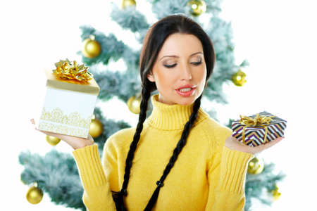 Beautiful brunette woman next to christmas tree on white background holding boxed gifts Stock Photo - 637351