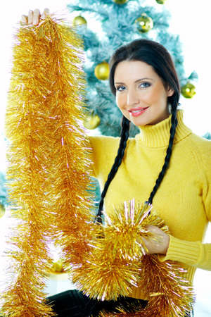 Beautiful brunette woman next to christmas tree with christmas chain on white background Stock Photo - 637349
