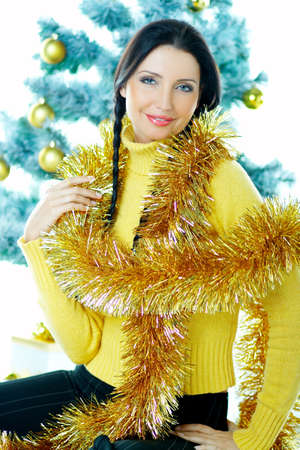 Beautiful brunette woman next to christmas tree with christmas chain on white background Stock Photo - 637350
