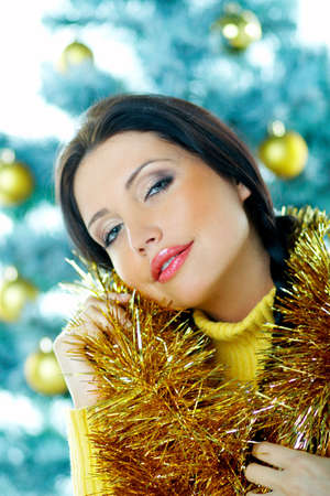 Beautiful brunette woman next to christmas tree with christmas chain on white background Stock Photo - 637348