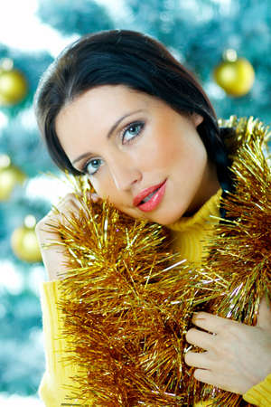 Beautiful brunette woman next to christmas tree with christmas chain on white background Stock Photo - 637346