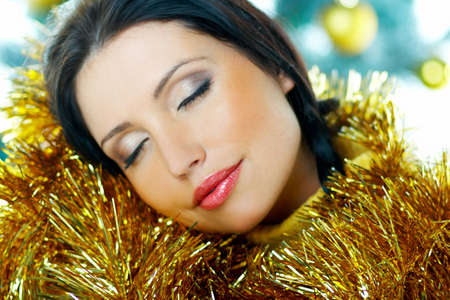Beautiful brunette woman next to christmas tree with christmas chain on white background Stock Photo - 636993