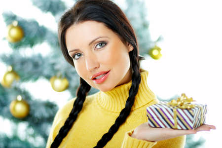 Beautiful brunette woman next to christmas tree on white background holding boxed gift photo