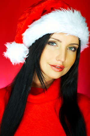 Portrait of beautiful brunette woman wearing santa claus hat on red background Stock Photo - 637286