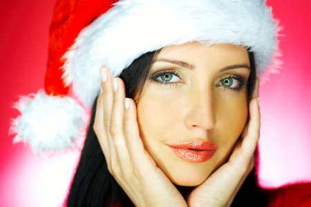 Portrait of beautiful brunette woman wearing santa claus hat on red background Stock Photo - 637283