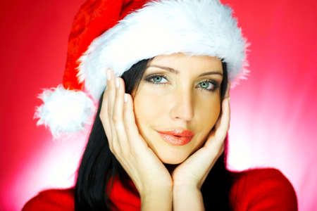Portrait of beautiful brunette woman wearing santa claus hat on red background Stock Photo - 637282