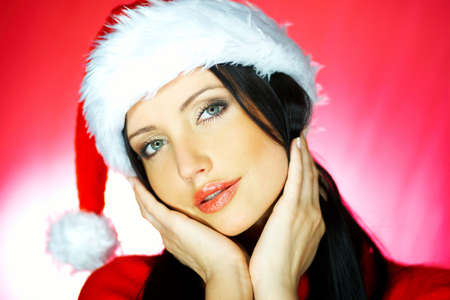 Portrait of beautiful brunette woman wearing santa claus hat on red background Stock Photo - 637185