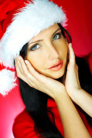 Portrait of beautiful brunette woman wearing santa claus hat on red background Stock Photo - 637184