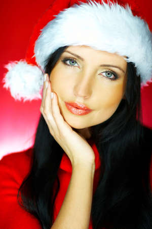 Portrait of beautiful brunette woman wearing santa claus hat on red background Stock Photo - 637182